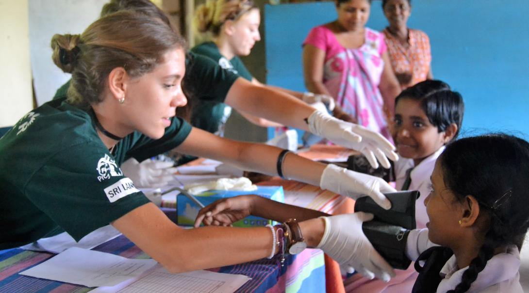 A group of medical volunteers abroad participate in a community healthcare outreach at a school in Asia.